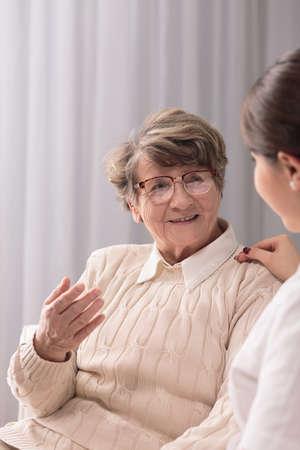 persona de la tercera edad: Cuadro de la señora mayor con la actitud positiva y el cuidador Foto de archivo