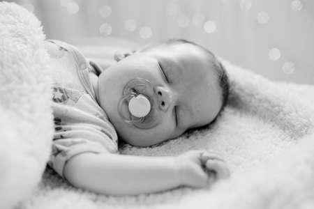 warmth: Calm newborn sleeping with dummy in mouth