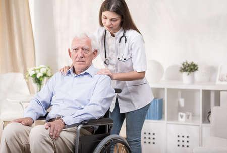 mujer trabajadora: Enfermera comunitaria con el viejo hombre discapacitado en silla de ruedas