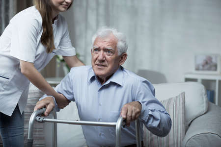 nursing assistant: Disabled man using a walking frame with help of the nurse Stock Photo