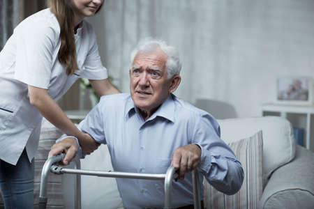 Gehandicapte man met behulp van een walking frame met behulp van de verpleegkundige