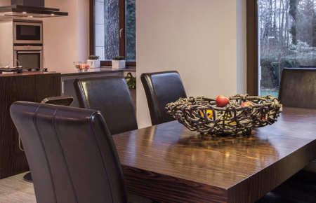 dining table and chairs: Close up of solid wooden dining table and leather chairs Stock Photo