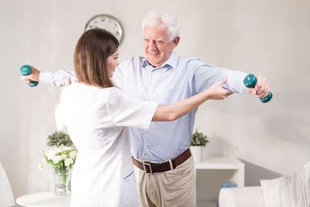 help: Nurse helping patient to exercise with dumbbels Stock Photo