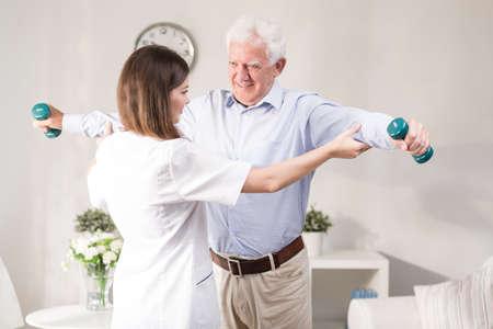 Zdravotní sestra pomáhá pacientovi vykonávat s činku
