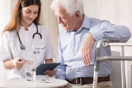 ageing: Dictrict nurse giving her sick senior patient medicines