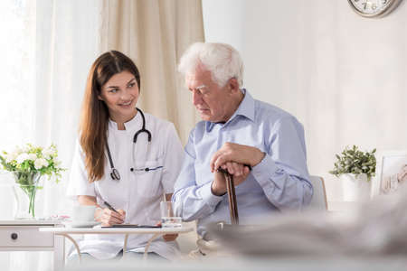 Elderly patient talking to young smiling community nurse