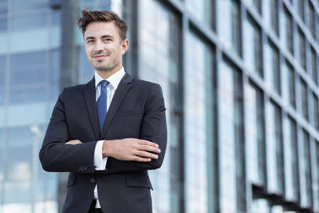 standing businessman: Young worker of corporation wearing elegant suit Stock Photo