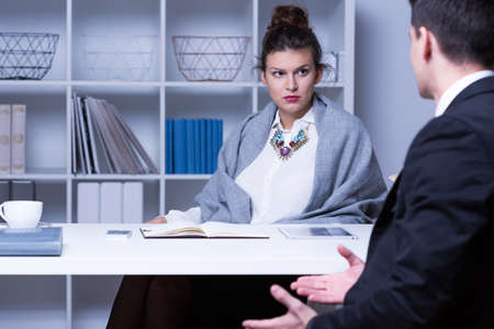 strict: Strict businesswoman sitting at the desk and talking with employee Stock Photo