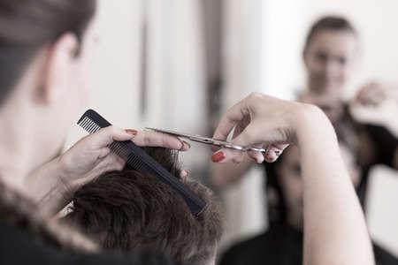 hair stylist: Female hair stylist cutting mans hair with scissors