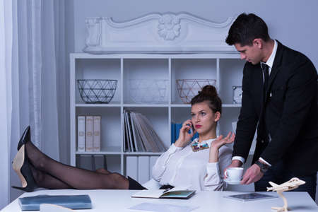 secretaries: Mujer de negocios arrogante con las piernas sobre el escritorio Foto de archivo