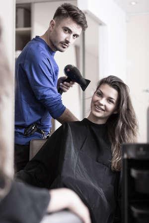 estilista: Estilista joven Cabello seco de clientes mujer pelo Foto de archivo
