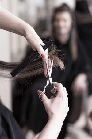 Vrouwelijke kapper knippen haar in haar salon Stockfoto