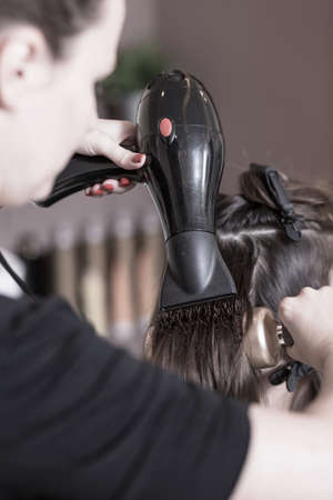 coax: Hairdresser using hairdryer and hairbrush at salon