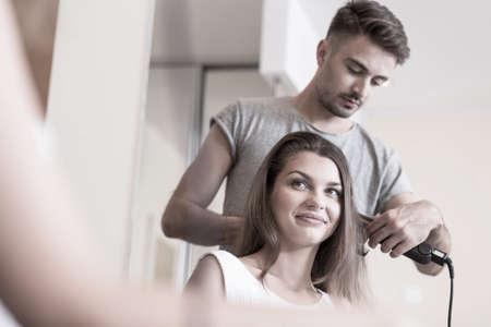 straightener: Hairdresser using hair straightener at hair salon