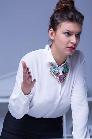 acoso laboral: Vista vertical de estricta gesticulando empresaria enojada
