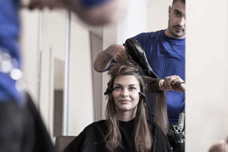 hair stylist: Hair stylist combing female hair at salon Stock Photo
