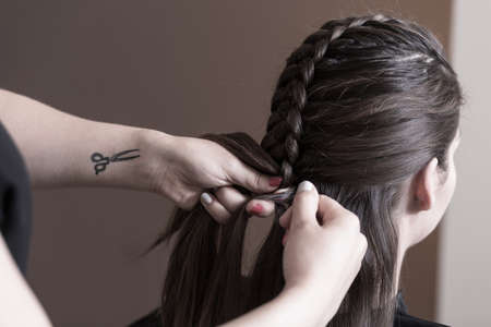 plait: Haidresser doing beautiful plait at hair salon