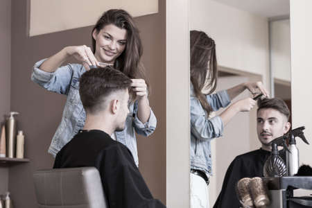 grows: Young female hairdresser cutting male clients hair