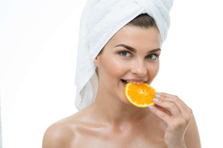 Horizontal image of beautiful refreshed woman in towel eating orange