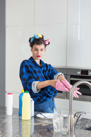 homemaker: Young woman cleaning the kitchen after dinner