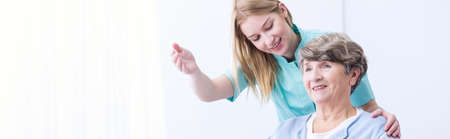 home care nurse: Young caregiver showing patient the room in nursing home Stock Photo