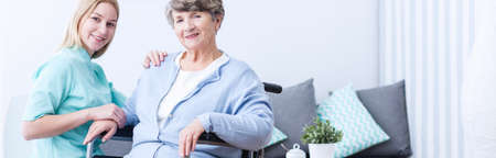 Senior happy woman and caring young nurse Stock Photo