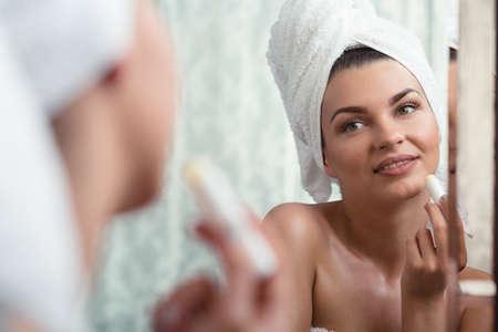nourishing: Horizontal photo of a female nourishing and moisturizing her lips