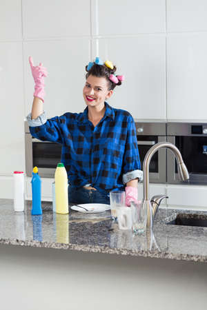 homemaker: Smiling housewife with hair rollers during housework Stock Photo