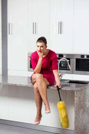house maid: Unhappy housewife sitting on the worktop in the kitchen Stock Photo
