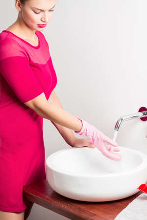 handbasin: Pedantic woman cleaning sink in rose gloves Stock Photo