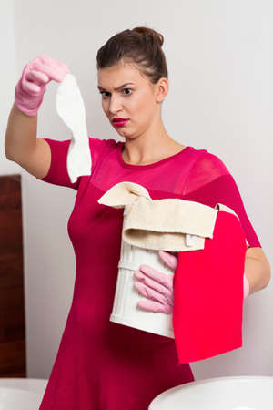 pedantic: Maid holding dirty sock and basket with clothes