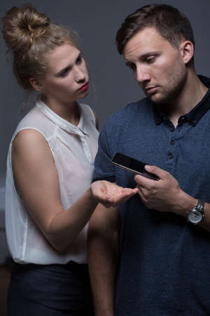 giving back: Man giving back the phone to check to his wife