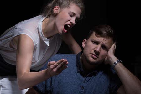 hombre pobre: Mujer joven agresiva gritando a su pobre Foto de archivo