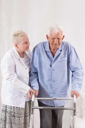 persona de la tercera edad: Hombre jubilado con discapacidad utilizando un andador con la ayuda de la enfermera Foto de archivo