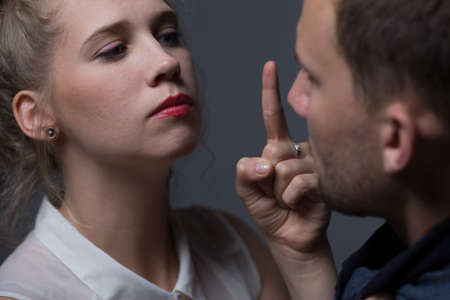 submissive: Beautiful imperative woman threatening to her husband Stock Photo