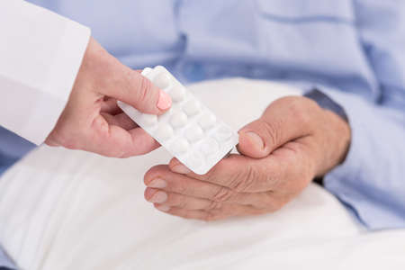 prescribe: Close-up of pills in blister pack hold in hand Stock Photo