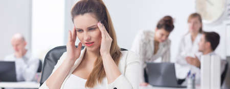terrible: Young beautiful businesswoman with terrible headache