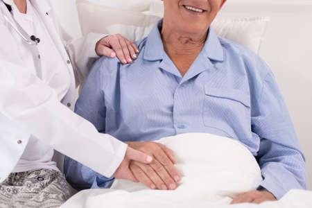 Verpleegster in witte toga met pensioen de hand patiënt Stockfoto - 49986492