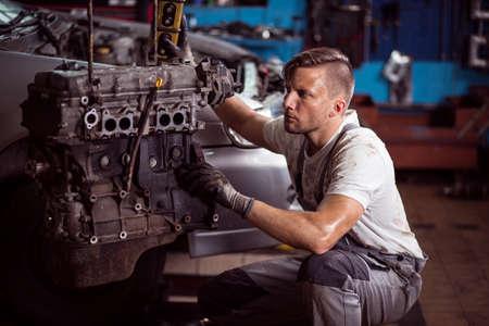 garage automobile: mécanicien de voitures et un moteur de voiture à l'extérieur du véhicule