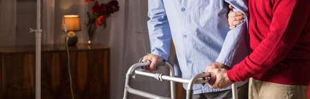 Older man walking with walker in caregiver's assistance Stockfoto