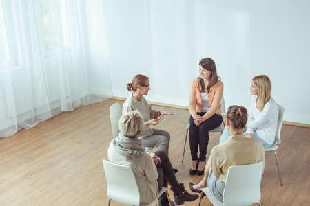 Smart elderly psychotherapist talking with her patients