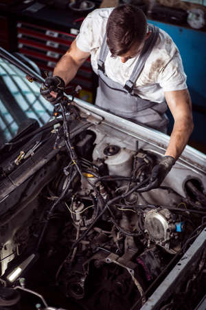dirty car: Dirty young mechanic checking car cables