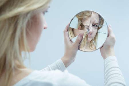 Ongelukkig mooi meisje met complexen en gebroken spiegel Stockfoto