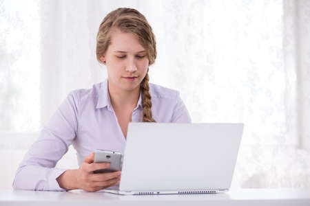 harassing: Photo of girl with laptop and cellphone responsible using technology Stock Photo