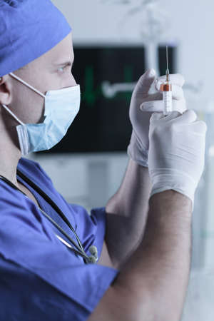doctor with mask: Vertical view of an anesthesiologist preparing narcosis injection for patient Stock Photo