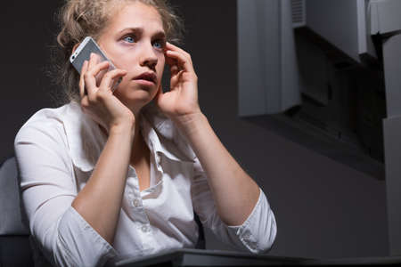answering: Woman is answering urgent telephone from boss Stock Photo