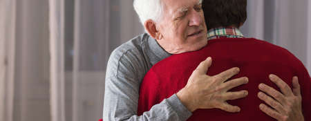 Older grateful man hugging his helpful caregiver