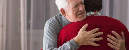 Oudere dankbaar man knuffelen zijn behulpzaam verzorger