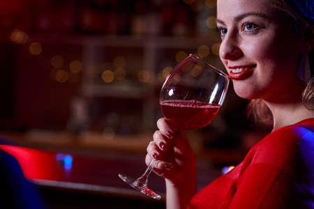 jovenes tomando alcohol: Muchacha sonriente en rojo beber vino vestido en la barra