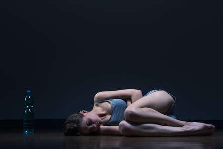 skinny: Imagen de la muchacha flaca acostado en el piso con la botella de agua